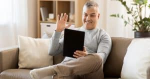 """A man waving at webinar attendees from his tablet. A featured image from the LOJO Marketing article, """"Five Actionable Ways To More Effectively Promote Your Virtual Event""""."""