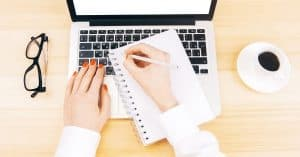 "A copy writer in front of a laptop, about to get started with a pen and notebook. | A featured image from ""How To Use the Power of Words in Marketing (to Effectively Boost Your Brand)"" by LOJO Marketing."